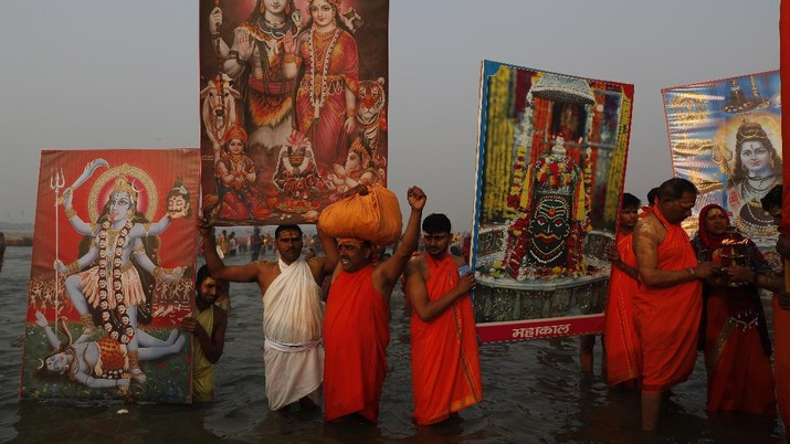 Devotees carry images of Hindu deities as they gather to take holy dips at Sangam, the confluence of the rivers Ganges and the Yamuna on 'Mauni Amavasya' or new moon day, an auspicious bathing day during the annual month long Hindu religious fair