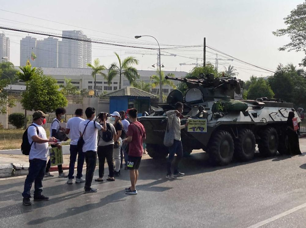 Anti-coup protesters stand in front of an armored personnel carrier deployed outside the Central Bank building in Yangon, Myanmar Monday, Feb. 15, 2021. Sightings of armored personnel carriers in Myanmar's biggest city and an internet shutdown raised political tensions late Sunday, after vast numbers of people around the country flouted orders against demonstrations to protest the military's seizure of power. (AP Photo)