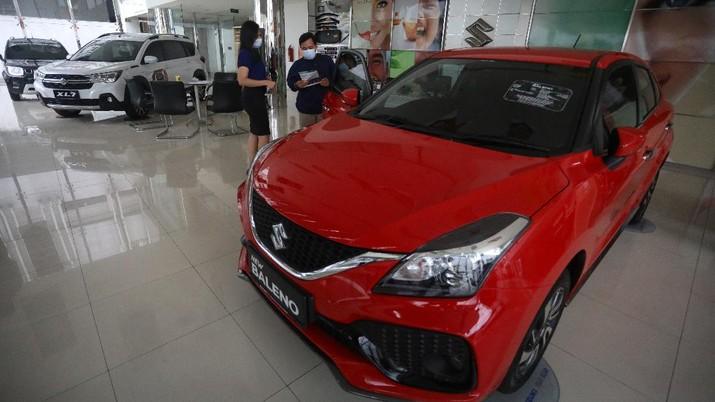 Calon pembeli melihat mobil baru di Showroom Suzuki di Kawasan Gading Serpong, Tangerang Selatan, Selasa (16/2/2021). Pemerintah memutuskan untuk memberikan insentif Pajak Penjualan Barang Mewah (PPnBM) atau pajak 0%. Insentif tersebut terbagi menjadi tiga tahap yang akan dievaluasi per tiga bulan. (CNBC Indonesia/Andrean Kristianto)