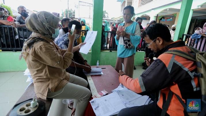 Warga menerima Bantuan Langsung Tunai (BLT) di Sawangan, Depok, Selasa (16/2/2021). Pemerintah melalui Kementerian Sosial (Kemensos) tahun ini melanjutkan penyaluran program Bantuan Sosial Tunai atau bantuan langsung tunai (BLT) secara bertahap melalui Kantor Pos. (CNBC Indonesia/Tri Susilo)