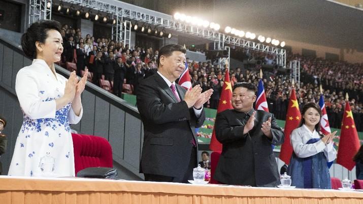 In this Thursday, June 20, 2019, photo released by China's Xinhua News Agency, visiting Chinese President Xi Jinping, second from left, and his wife Peng Liyuan, left, and North Korean leader Kim Jong Un, second from right, and his wife Ri Sol Ju, right, applaud during a mass gymnastic performance at the May Day Stadium in Pyongyang, North Korea. North Korean leader Kim Jong Un, meeting in Pyongyang with Chinese President Xi Jinping, said Thursday that his country is waiting for a desired response in stalled nuclear talks with the United States. (Huang Jingwen/Xinhua via AP)