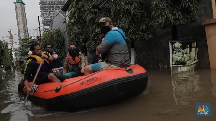 Warga melintas di komplek perumahan yang terendam banjir di Jatibening Permai, Bekasi, Jawa Barat, Jumat 19/2. Hujan yang mengguyur Kota Bekasi menyebabkan banjir di sejumlah titik. Bahkan ketinggian banjir di Perumahan Jatibening Permai mencapai perut orang dewasa. Hingga kini banjir belum juga surut. Peroses evakuasi masih berjalan. Perahu karet disiapkan untuk evakuasi warga yang masih di dalam perumahan. Diketahui terdapat 6 Kecamatan di Kota Bekasi yang tergenang akibat hujan. (CNBC Indonesia/ Muhammad Sabki)