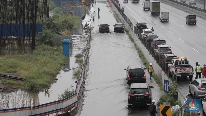 Petugas berjaga di bawah papan bertuliskan pengalihan arus karena genangan di Tol Jatibening, Jakarta, Jumat 19/2. Hujan semalaman yang mengguyur kawasan Jabodetabek membuat berbagai wilayah kebanjiran. Sejumlah kawasan tol pun terdampak banjir dan lumpuh. Akses masuk Gerbang Tol Jatibening arah Jakarta terpantau genangan. Tepatnya terjadi di lajur masuk Jatibening atau Cawang. Khusus kendaraan besar tetap dapat melintas, sementara kendaraan kecil golongan 1 dialihkan ke ruas Jalan Tol Dalam Kota. (CNBC Indonesia/ Muhammad Sabki)