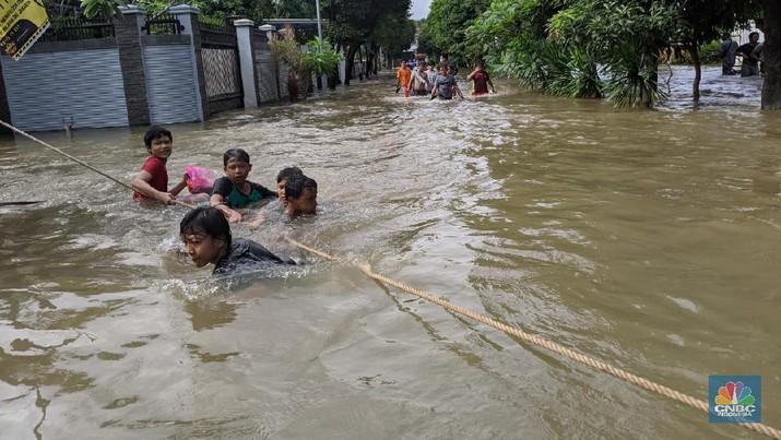Banjir di Kawasan Bumi Harapan Permai, Kampung Dukuh, Kramat Jati, Jakarta Timur.  Akibat intensitas hujan lebat, Jumat  (19/Februari/2021) kemarin. Menurut Satpam yang bertugas Syahrul, air mulai masuk di kawasan komplek pada pukul 2.00 dini hari melalui anak kali Cipinang. Ditambah hujan yang belum berhenti hingga pukul 13.00 Ketinggian banjir terdalam mencapai dada orang dewasa orang dewasa. Bahkan di beberapa blok harus dievakuasi dengan perahu karet.(CNBC Indonesia/Emir)