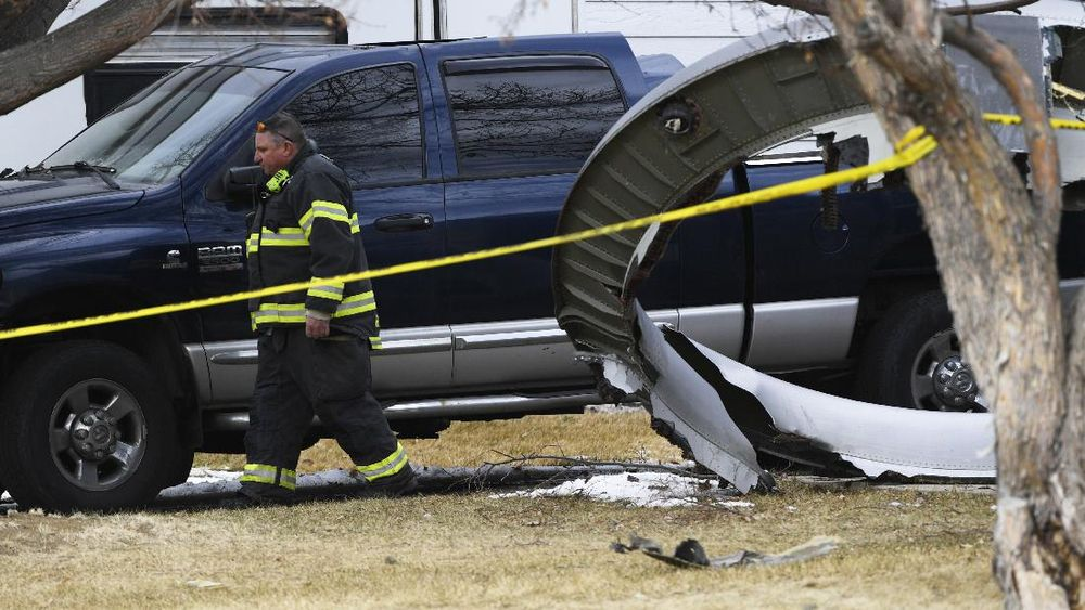 A North Metro firefighter walks past a large piece of an airplane engine in the front yard of a home on Elmwood Street near E. 13th Avenue, Saturday, Feb. 20, 2021, in Broomfield, Colo. Debris from a United Airlines plane fell onto Denver suburbs during an emergency landing Saturday after one of its engines suffered a catastrophic failure and rained pieces of the engine casing on a neighborhood where it narrowly missed a home. (Andy Cross/The Denver Post via AP)