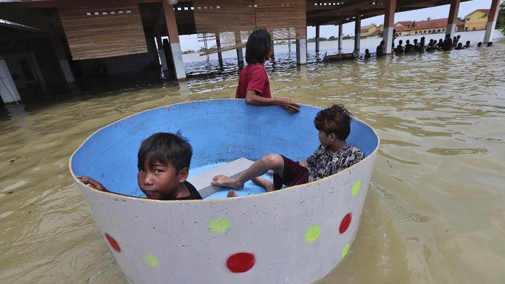 Indonesian youths play in the water during a flood in Bekasi, Indonesia, Monday, Feb. 22, 2021. Thousands of residents are being evacuated on the outskirts of Indonesia's capital amid flooding after the Citarum River embankment broke, officials said Monday. (AP Photo/Achmad Ibrahim)