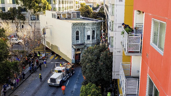 CORRECTS APPROXIMATE COST TO $400,000, INTEAD OF $200,000 - Crowds watch as a truck pulls a Victorian home through San Francisco on Sunday, Feb. 21, 2021. The house, built in 1882, was moved to a new location about six blocks away to make room for a condominium development. According to the consultant overseeing the project, the move cost approximately $400,000 and involved removing street lights, parking meters, and utility lines. (AP Photo/Noah Berger)