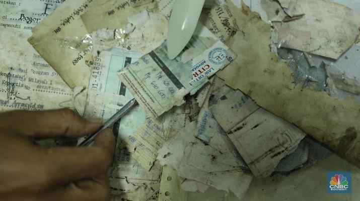 Petugas restorasi ARSIP Nasional Republik Indonesia (ANRI) melakukan perbaikan dokumen milik warga yang terdampak banjir, Jakarta, Senin ( 22/2/2021). Dokumen yang rusak seperti Ijazah hingga akte kelahiran akan diperbaiki 1 sampai 4 Minggu. Contoh arsip keluarga yang bisa diperbaiki dari kerusakan banjir adalah akte, surat perkawinan, akte kelahiran, surat kematian, STTB dll. Maksimal berkas yang diterima 10 lembar.  (CNBC Indonesia/ Tri Susilo)