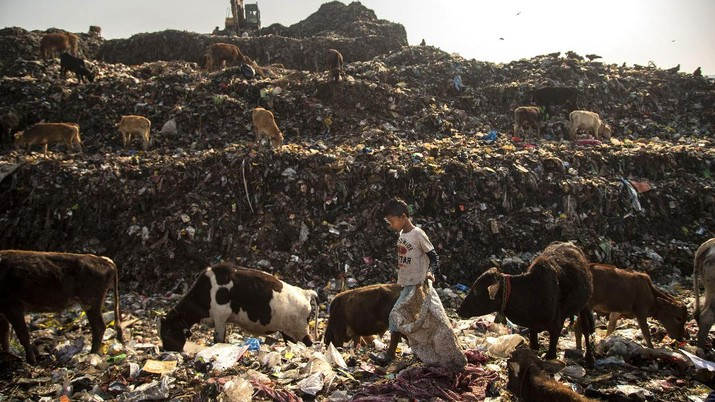"Imradul Ali, 10, left, and his mother Anuwara Beghum, 30, take a break as they look for recyclable material at a landfill on the outskirts of Gauhati, India, Thursday, Feb. 4, 2021. Once school is done for the day, Ali, rushes home to change out of his uniform so that he can start his job as a scavenger in India's remote northeast. Coming from a family of scavengers or ""rag pickers,"