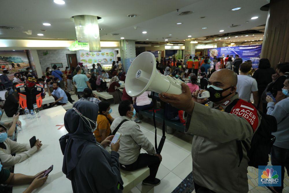 Petugas gabungan membubarkan kerumunan antrian vaksinasi pedagang di Pasar Tanah Abang, Jakarta, Selasa (23/2/2021). Sejumlah pedagang masih bertahan dilokasi ujtuk menunggu informasi lebih lanjut. Wina (43) pedagang pakaian Blok A menjelaskan, antrian mulai mengular mulai pukul 10.00 wib di lantai 8 hingga 9, kerumunan juga terjadi karena antrian tidak menggunakan nomor antrian jelasnya. Pantauan CNBC Indonesia dilapangan pedagang masih ada yang menunggu di lantai 8 untuk meminta info lebih lanjut untuk penyuntikan vaksin. (CNBC Indonesia/ Tri Susilo)