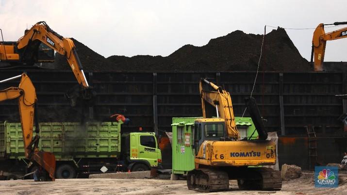 Pekerja melakukan bongkar muat batu bara di Terminal Tanjung Priok, Jakarta, Selasa (23/2/2021). Pemerintah telah mengeluarkan peraturan turunan dari Undang-Undang No. 11 tahun 2020 tentang Cipta Kerja. Adapun salah satunya Peraturan Pemerintah yang diterbitkan yaitu Peraturan Pemerintah No.25 tahun 2021 tentang Penyelenggaraan Bidang Energi dan Sumber Daya Mineral.  (CNBC Indonesia/ Tri Susilo)