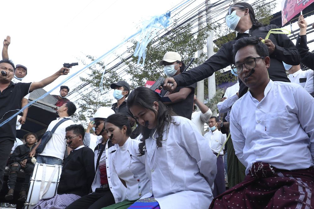 Anti-coup protesters depict the plight of civil servants being forced to work at gunpoint by the military junta during a rally in Mandalay, Myanmar, Monday, Feb. 22, 2021. A call for a Monday general strike by demonstrators in Myanmar protesting the military's seizure of power has been met by the ruling junta with a thinly veiled threat to use lethal force, raising the possibility of major clashes. (AP Photo)