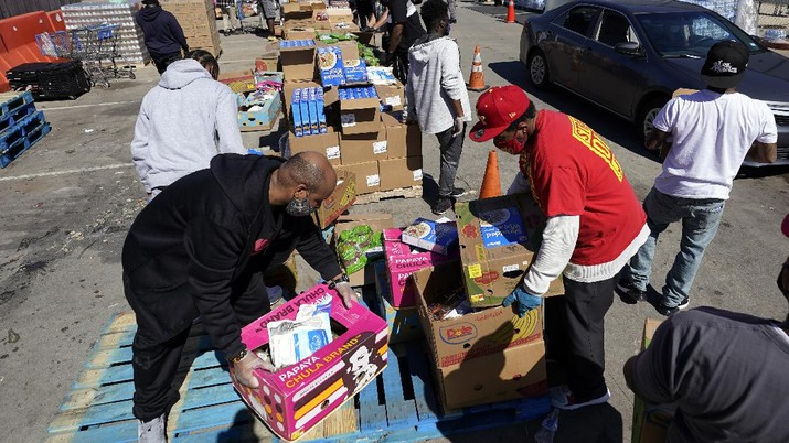 Volunteers load vehicles with food and water at a distribution site Monday, Feb. 22, 2021, in Houston. The city's boil water notice has been rescinded however many residents lack water at home due to broken pipes. (AP Photo/David J. Phillip)