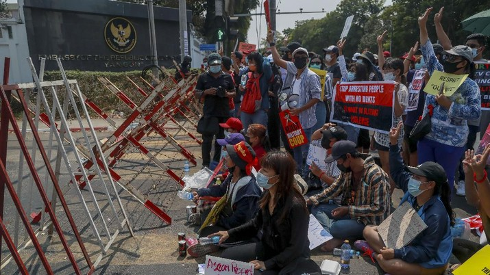 A policeman stands guard as demonstrators display placards during a protest close to Indonesian embassy in Yangon, Myanmar Tuesday, Feb. 23, 2021. Anti-coup protesters gathered outside the Indonesian Embassy following reports that Indonesia was seeking to have fellow members of the Association of Southeast Asian Nations to agree on an action plan over the Myanmar's coup that would hold the junta  to its promise to hold free and fair elections in a year's time. The Indonesia Foreign Ministry has denied the report. (AP Photo)