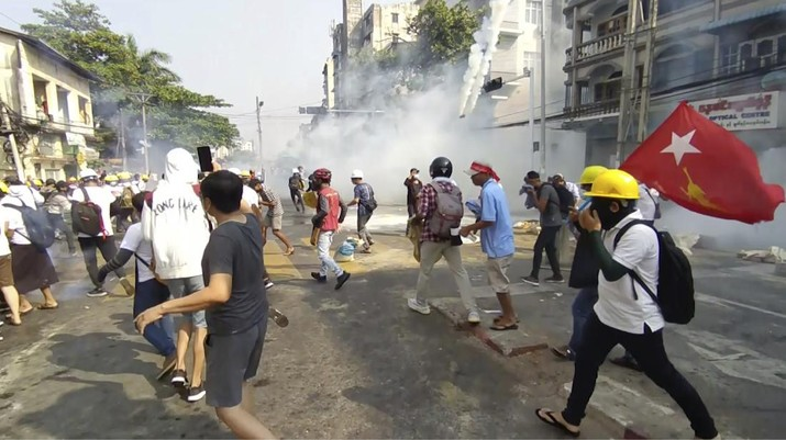 In this image from a video, anti-coup protesters react as smoke from tear gas rises in Yangon, Myanmar Sunday, Feb. 28, 2021. Police fired tear gas and water cannons and there were reports of gunfire Sunday in Myanmar's largest city where another anti-coup protest was underway with scores of students and other demonstrators hauled away in police trucks. (AP Phoro)