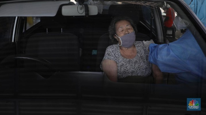 Warga lansia menjalani vaksinasi Covid-19 secara Drive thru di Kawasan Kemayoran, Jakarta, Rabu, (3/3/2021). Layanan vaksinasi COVID-19 untuk lansia secara drive thru dimulai pada Rabu, 3 Maret hingga akhir tahun 2021. (CNBC Indonesia/Muhammad Sabki)
