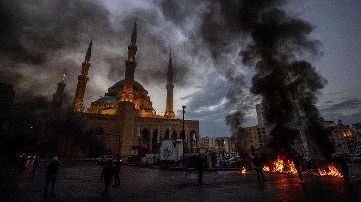 Warga Lebanon marah memblokir seluruh jalan dengan membakar ban dan tempat sampah setelah mata uang Lebanon jatuh ke titik terendah baru dalam krisis ekonomi. (AP/Hassan Ammar)
