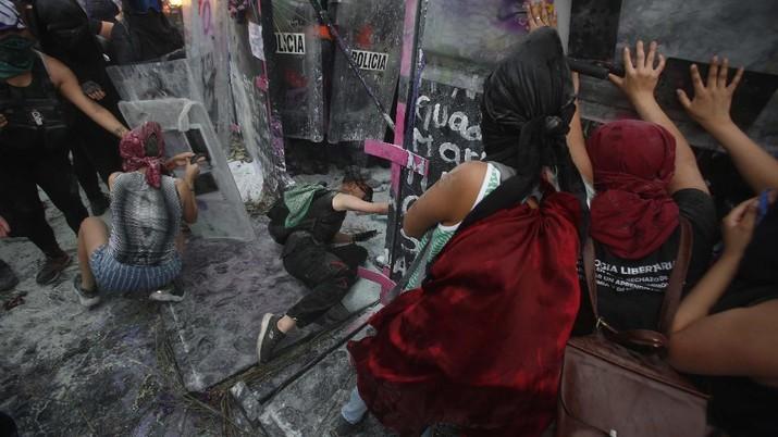 Pasukan polisi dan para aktivis terlibat bentrok di ibu Kota Meksiko di tengah aksi unjuk rasa memperingati Hari Perempuan Internasional, Senin (8/3/2021). (AP/Rebecca Blackwell)