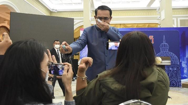 Perdana Menteri Thailand Prayuth Chan-ocha menyemprotkan alkohol disinfektan ke barisan depan wartawan yang duduk di dalam ruang konferensi pers di Government House di Bangkok, Thailand, Selasa, 9 Maret 2021.(AP Photo)