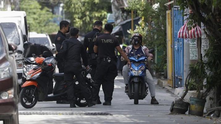 A cat crosses an empty street at a village that was placed under lockdown due to the number of COVID-19 cases among residents in Manila, Philippines on Thursday, March 11, 2021. The Philippine capital placed two villages and two hotels on lockdown Thursday and police have renewed warnings against kissing and other