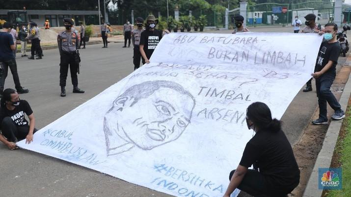 Sejumlah aktivis melakukan aksi simbolik menuntut Presiden Joko Widodo untuk mencabut Omnibus Law UU Cipta Kerja dan regulasi turunannya yang menghapus Fly Ash Bottom Ash (FABA) dari daftar limbah B3.di Kawasan Patung Kuda, Jakarta, 18 Maret 2021. (CNBC Indonesia/ Tri Susilo)