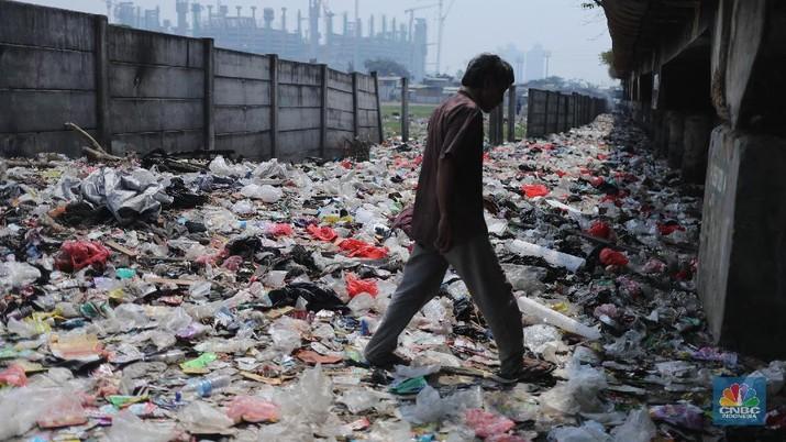 Warga melintas di kolong tol  Ir Wiyoto, Kelurahan Papanggo, Tanjung Priok, Jakarta, Kamis (18/3/2021). Tumpukan sampah plastik makanan dan limbah rumah tangga Tampak sudah melebur dengan tanah. Pantauan CNBC Indonesia di lokasi warga masih ada yang membuang sampah dilokasi walaupun sudah di tegur dengan warga sekitar. Yanto salah satu warga mengatakan