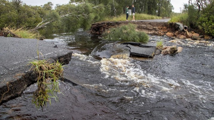 People stand at a washed out section of road at Port Stephens 200 kilometers (124 miles) north of Sydney, Australia, Saturday, March 20, 2021. People across New South Wales have been warned to expect intense rain and potentially life-threatening flooding, with Sydney predicted to be deluged with up to 200 millimeters of rain in one day. (AP Photo/Mark Baker)