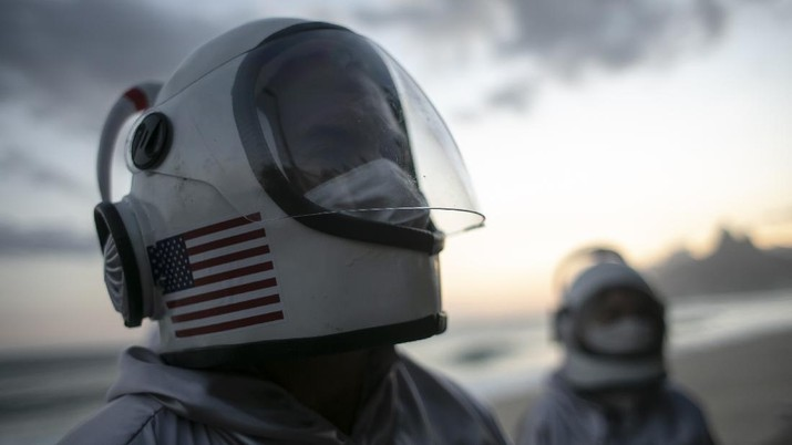 Accountant Tercio Galdino and wife Alicea, dressed in their astronaut costumes, watch as bystanders make photos of them on Ipanema beach in Rio de Janeiro, Brazil, Saturday, March 20, 2021. The Galdinos have come up with a unique way for protecting themselves and drawing awareness around COVID-19 protective measures – by dressing as astronauts. The pair first began to traverse the iconic beaches fully suited in mid 2020 at the height of the first wave of the pandemic in Brazil, now as cases surge once again they are taking their 'astronaut walks' back to the promenades. (AP Photo/Bruna Prado)