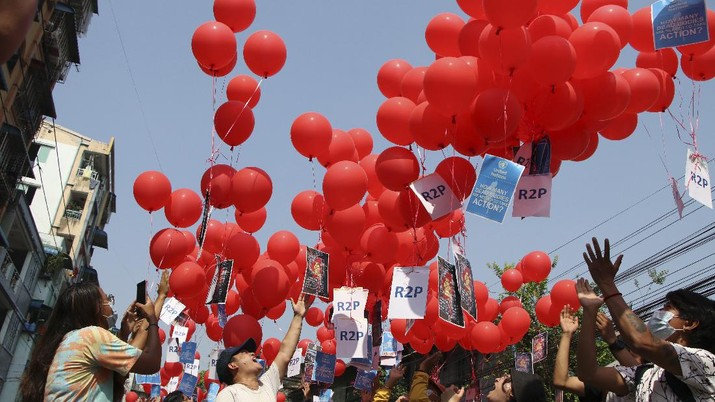 Anti-coup protesters hold red balloon, calling for foreign intervention to aid them in downtown Yangon, Myanmar, Monday, March 22, 2021. Protests against the coup continued in cities and town across the country, including Mandalay and Yangon. (AP Photo)