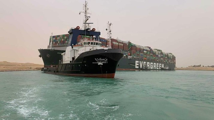 In this photo released by the Suez Canal Authority, a boat navigates in front of a massive cargo ship, named the Ever Green, rear, sits grounded Wednesday, March 24, 2021, after it turned sideways in Egypt's Suez Canal, blocking traffic in a crucial East-West waterway for global shipping. An Egyptian official warned Wednesday it could take at least two days to clear the ship. (Suez Canal Authority via AP)