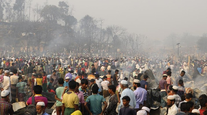 Rohingya refugees stand at the site of Monday's fire at a refugee camp in Balukhali, southern Bangladesh, Tuesday, March 23, 2021. Rescuers recovered more than a dozen charred bodies from a Rohingya refugee camp in southern Bangladesh after a devastating fire that destroyed thousands of shelters, officials said Tuesday. (AP Photo/ Shafiqur Rahman)