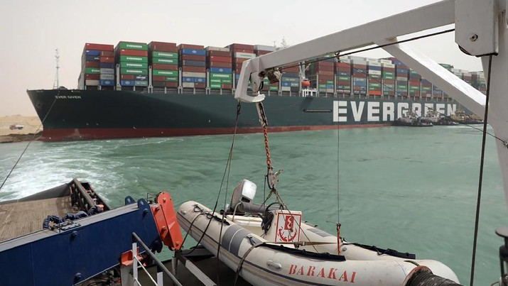 This photo released by the Suez Canal Authority on Thursday, March 25, 2021, shows the Ever Given, a Panama-flagged cargo ship, after it become wedged across the Suez Canal and blocking traffic in the vital waterway. An operation is underway to try to work free the ship wedged across Egypt's Suez Canal, which further imperiled global shipping Thursday as at least 150 other vessels needing to pass through the crucial waterway idled waiting for the obstruction to clear. (Suez Canal Authority via AP)