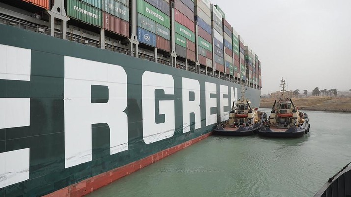 This photo released by the Suez Canal Authority on Thursday, March 25, 2021, shows two tugboats next to the Ever Given, a Panama-flagged cargo ship, after it become wedged across the Suez Canal and blocking traffic in the vital waterway from another vessel. An operation is underway to try to work free the ship, which further imperiled global shipping Thursday as at least 150 other vessels needing to pass through the crucial waterway idled waiting for the obstruction to clear. (Suez Canal Authority via AP)