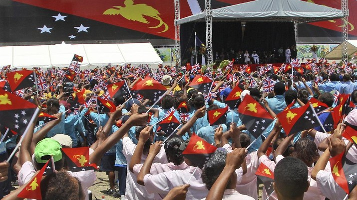 Thousands of children wave flags while performing for Britain's Prince Charles and his wife Camilla, Duchess of Cornwall, during a cultural display in Port Moresby , Papua New Guinea, Sunday, Nov. 4, 2012. The royal couple are in Papua New Guinea for three days, followed by a visit to Australia and New Zealand.  (AP Photo/Rob Griffith)