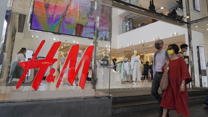 People walk past an H&M clothing store in Hong Kong, Saturday, March 27, 2021. H&M disappeared from the internet in China as the government raised pressure on shoe and clothing brands and announced sanctions Friday, March 26, 2021, against British officials in a spiraling fight over complaints of abuses in the Xinjiang region. (AP Photo/Kin Cheung)