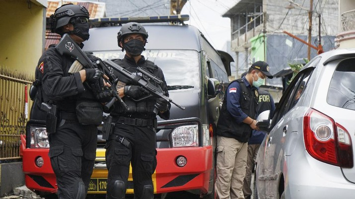 Police officers stand guard during a raid on a house that, police believe, is linked to the suicide bombers of Sunday's church attack, in Makassar, South Sulawesi, Indonesia, Monday, March 29, 2021. Two attackers believed to be members of a militant network that pledged allegiance to the Islamic State group blew themselves up outside the packed Roman Catholic cathedral during a Palm Sunday Mass on Indonesia's Sulawesi island, wounding a number of people, police said. (AP Photo/Daeng Mansur)