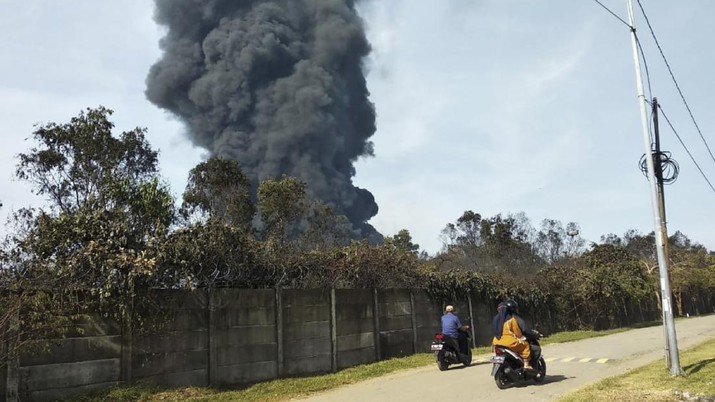 Motorists ride past as thick smoke billows from a fire that razes through Pertamina Balongan Refinery in Indramayu, West Java, Indonesia, Monday, March 29, 2021. Hundreds of people living in villages around the refinery have been evacuated following the fire that broke out after midnight on Monday. (AP Photo)