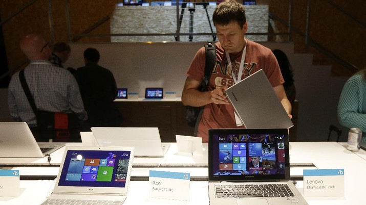 An Acer Aspire laptop, left, and a Lenovo IdeaPad U310 Touch are seen at a demo table at a Microsoft event in San Francisco, Wednesday, June 26, 2013. (AP Photo/Jeff Chiu)