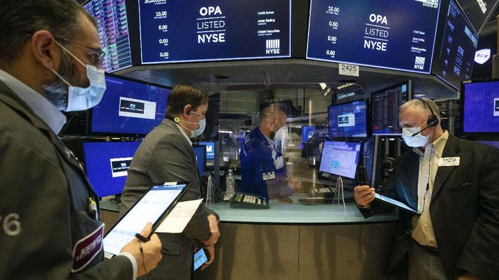 In this photo provided by the New York Stock Exchange, trader Americo Brunetti works on the floor, Thursday, March 25, 2021. Stocks are wobbling in afternoon trading Thursday as a slide in technology companies is being offset by gains for banks as bond yields stabilize.(Courtney Crow/New York Stock Exchange via AP)
