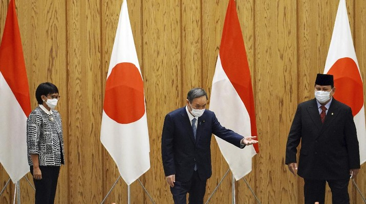 Japan's Prime Minister Yoshihide Suga, center, walks with Indonesian Foreign Minister Retno Marsudi, left, and Indonesian Defense Minister Prabowo Subianto after a photo session at the prime minister's official residence in Tokyo Tuesday, March 30, 2021. The Indonesian ministers are visiting Tokyo for security discussions focusing on China's growing assertiveness in regional seas. (AP Photo/Eugene Hoshiko, Pool)