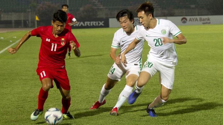 Hein Htet Aung dari Myanmar, kiri, bersaing memperebutkan bola dengan Wan Tin Iao dari Macau, kanan, dan Leung Chi Seng pada babak kualifikasi sepak bola Kejuaraan AFC U-23 2020, Minggu, Maret. 24, 2019, di Stadion Thuwunna, Yangon, Myanmar. Myanmar menang 4-0. (FILE FOTO/Foto AP / Thein Zaw)