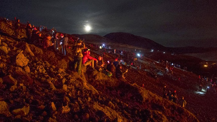 People watch as lava flows from an eruption of a volcano on the Reykjanes Peninsula in southwestern Iceland late on Monday, March 29, 2021. Iceland's latest volcano eruption is still attracting crowds of people hoping to get close to the gentle lava flows. The eruption in Geldingadalur, near Iceland's capital Reykjavik, is not seen as a threat to nearby towns and the slow flows mean people can get close to action without too much harm. (AP Photo/Marco Di Marco)