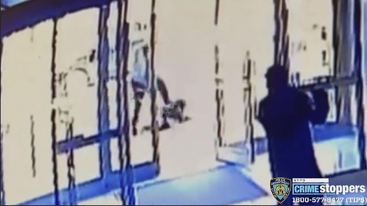This image taken from surveillance video provided by the New York City Police Department shows a person of interest, background center, assaulting an Asian American woman, on ground, Monday, March 29, 2021, in New York. The 65-year-old woman was walking in midtown Manhattan a few blocks from Times Square on Monday afternoon when a man approached her and kicked her in the stomach, knocking her to the ground, police said.  (Courtesy of New York Police Department via AP)