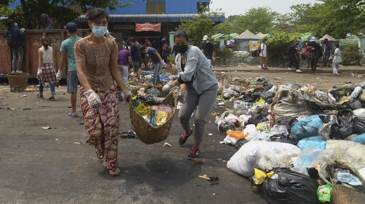 Anti-coup protesters use garbage to block a road as a form of