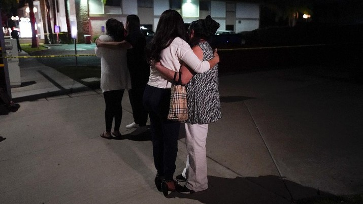 Unidentified people comfort each other as they stand near a business building where a shooting occurred in Orange, Calif., Wednesday, March 31, 2021. Police say several people were killed, including a child, and the suspected shooter was wounded by police. (AP Photo/Jae C. Hong)