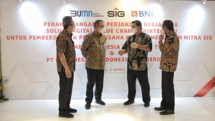 Direktur Utama BNI Royke Tumilaar (kedua kiri), Direktur Utama PT Semen Indonesia (Persero) Tbk Hendi Prio Santoso (kedua kanan), Direktur Bisnis UMKM BNI Muhammad Iqbal (kanan), dan Direktur Keuangan PT Semen Indonesia (Persero) Tbk Doddy Sulasmono (kiri) berbincang-bincang pasca penandatanganan Perjanjian Kerja Sama (PKS) Solusi Digital Value Chain Terintegrasi untuk Pemberdayaan Pelaku Usaha Kecil dan Menengah Mitra SIG di Jakarta, Senin (5 April 2021). BNI memberikan kepada PT Semen Indonesia (Persero) Tbk layanan solusi transaksional terintegrasi yang unggul melalui fasilitas pembiayaan value chain dengan menggunakan platform BNI Financial Supply Chain Management. (Dok. BNI)