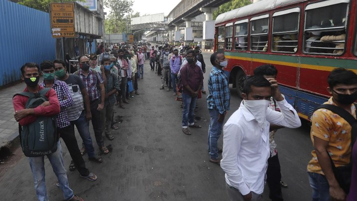 People wearing masks queue up to board buses in Mumbai, India, Monday, April 5, 2021. India reported its biggest single-day spike in confirmed coronavirus cases since the pandemic began Monday, and officials in the hard-hit state home to Mumbai are returning to the closure of some businesses and places of worship in a bid to slow the spread. (AP Photo/Rafiq Maqbool)