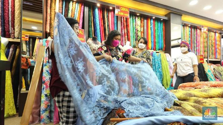 Pembeli memilih kain di salah satu toko tekstil di Pasar Baru, Jakarta, Selasa (6/4/2021). Pemerintah didesak untuk segera memberlakukan penerapan safequard atau perlindungan karena makin markanya produksi tekstil impor di Indonesia. Sekjen Asosiasi Pertekstilan Indonesia, Rizal Tanzil Rakhman menyebutkan bahwa industri tekstil dan produk tekstil (TPT) sektor kain atau garmen saat ini tengah menghadapi gempuran impor kain yang mencapai 46 persen. Pantauan CNBC Indonesia kain didatangkan langsung dari Tiongkok, India dan Italia (CNBC Indonesia/ Tri Susilo)