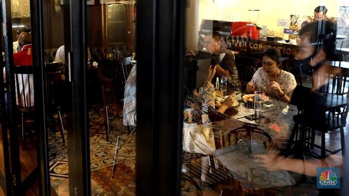 Petugas membersihkan meja makanan di Restoran di Kawasan Benhil, Jakarta, Selasa 6/4. Perhimpunan Hotel dan Restoran Indonesia (PHRI) Jakarta ingin pemerintah meningkatkan kapasitas jumlah pengunjung yang bisa makan di tempat alias dine in di tempat makan menjadi 75 persen saat masa buka bersama (bukber) puasa sepanjang Ramadan. Saat ini, kapasitas pengunjung dine in hanya boleh 50 persen. Kebijakan ini diterapkan karena pemerintah masih melangsungkan Pemberlakuan Pembatasan Kegiatan Masyarakat (PPKM) Mikro. Terkait hal ini, Pelaksana Tugas (Plt) Kepala Dinas Pariwisata dan Ekonomi Kreatif DKI Jakarta Gumilar Ekalaya mengatakan belum ada perubahan aturan terkait kapasitas jam operasional restoran saat momen buka puasa bersama seperti dikutip CNN Indonesia. Namun, pemerintah tetap membuka masukan dari pengusaha. Pelaksana tugas (Plt) Kepala Dinas Pariwisata dan Ekonomi Kreatif DKI Jakarta, Gumilar Ekalaya juga mengatakan pihaknya tidak melarang pelaksanaan kegiatan buka puasa bersama (bukber) di restoran atau rumah makan di masa pandemi Covid-19. Menurut Gumilar, waktu pelaksanaan kegiatan bukber tidak melanggar ketentuan dalam PPKM Mikro. Meski tidak melarang, Gumilar mengingatkan kegiatan buka bersama harus tetap menerapkan protokol kesehatan. (CNBC Indonesia/Muhammad Sabki)