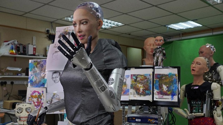 David Hanson, left, creator of Sophia, shows a work of Sophia at his studio in Hong Kong on March 29, 2021. Sophia is a robot of many talents — she speaks, jokes, sings and even makes art. In March, she caused a stir in the art world when a digital work she created as part of a collaboration was sold at an auction for $688,888 in the form of a non-fungible token (NFT).WLD(AP Photo/Vincent Yu)